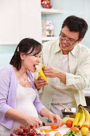 Asian couple activity in kitchen, with lots of fruit and vegeteable, where the couple eating fruit Stock Photo - 9564724