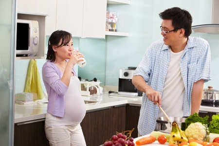 Pregnant wife drinking milk while watching her husband cooking
