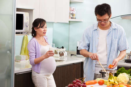 Pregnant wife drinking milk while watching her husband cooking Stock Photo - 9564719
