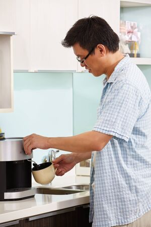 Asian male making coffee at kitchen in the morning photo