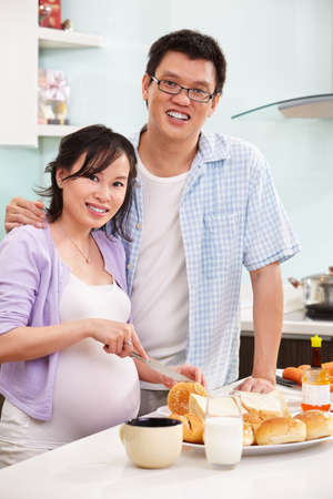 Chinese couple ( pregnant wife with her husband )  preparing breakfast in the kitchen photo