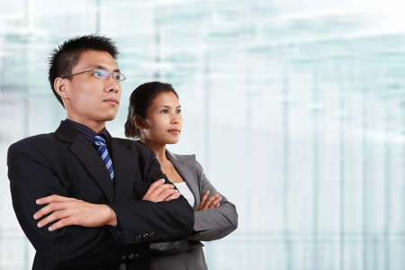 Two successful Asian business people looking at empty space, with blur glass windows as background photo