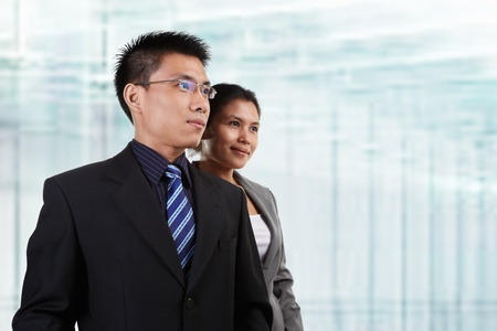 asian office lady: Two Asian business people pose together with blur glass windows as background