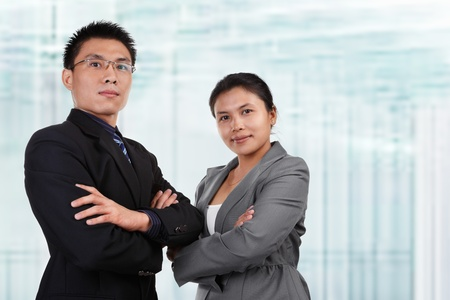 Two Asian business people pose together with blur glass windows as background photo