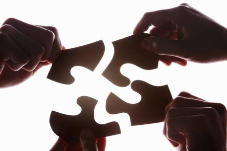 uncommon: Hands try to solve the uncommon shape puzzle, taken in silhouette against bright white background Stock Photo