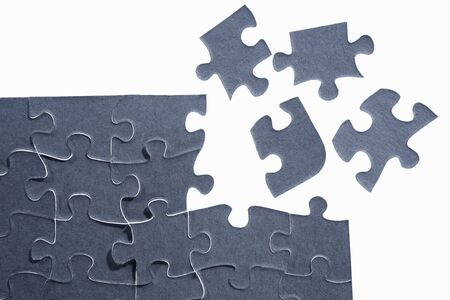 jigsaw puzzle piece: Unfinished puzzle at the corner with four segmented pieces scatter