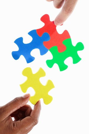 jigsaw piece: Hand trying to connect the colorful jigzaw puzzle pieces