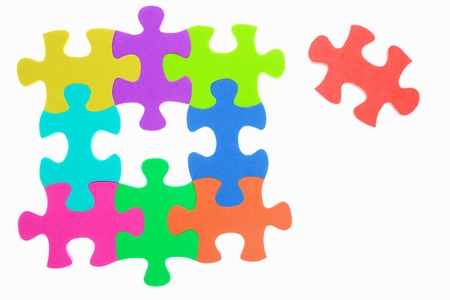 unattached: Colorful jigzaw puzzle with the last one unattached, isolated over white background Archivio Fotografico