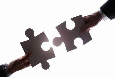 Business peoples hands connecting two jigzaw puzzle pieces. Silhouette against bright white background