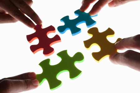 puzzle pieces: Hand versucht, vier St�cke des Jigzaw Puzzle anschlie�en. Gedreht genommen mit Hintergrundbeleuchtung, geringe Tiefensch�rfe