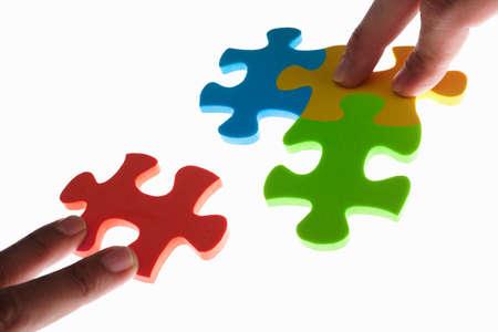 toma de decision: Manos intentando conectar dos piezas del puzzle de colores jigzaw. Disparo adoptadas con luz de fondo, una profundidad superficial de campo Foto de archivo