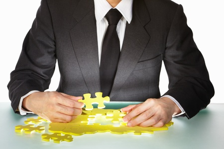 Unrecognizable Businessman trying to finish the puzzle photo