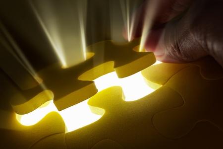 descubrir: Foto de concepto con pieza de puzzle con rayo de luz que sale de la pieza que faltaba