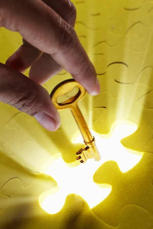 gold key: Concept photo using piece of puzzle with ray of light comes out from missing piece Stock Photo