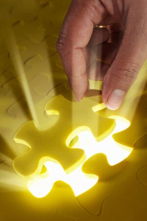 Concept photo using piece of puzzle with ray of light comes out from missing piece photo