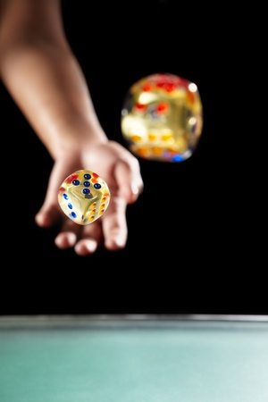 Hand throwing two dices, over dark background photo