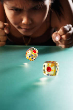 Young Asian woman expressing her hopr to get big number on rolling dices photo