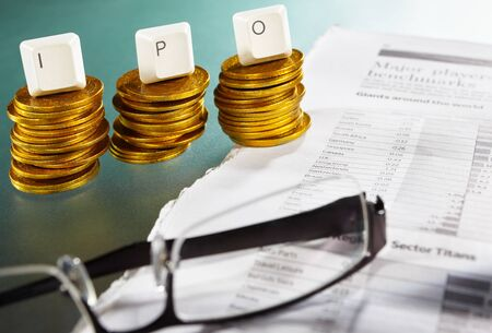 IPO letter on each block over gold coins stacks with newspaper and glasses Stock Photo