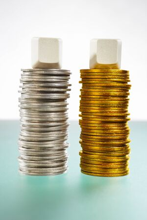 Two stack of silver and gold coins with blank block on top of each stacks Stock Photo - 9112992