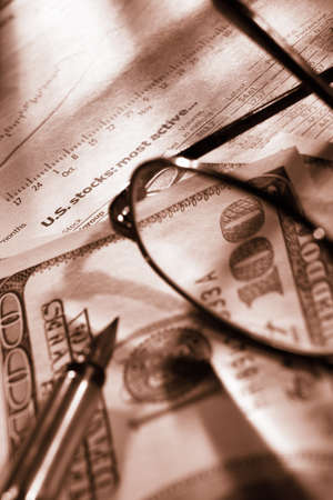 echange: Glasses, pen and dollar bills over stock echange data paper. Very shallow depth of field.