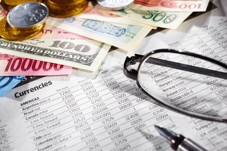foreign exchange: Glasses over the foreign exchange sheet with money from different countries on edge Stock Photo