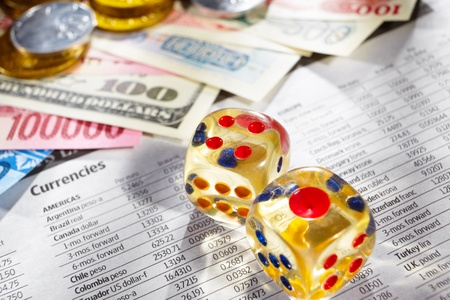 Two dices over the foreign exchange sheet with money from different countries on edge photo