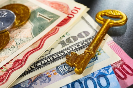Golden key over money from different countries photo