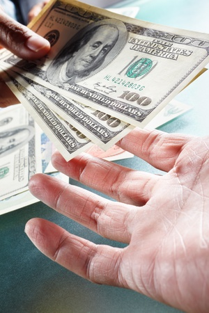 Two people on money exchange, taken cloese up, with one hand handing over US dollar bills Stock Photo