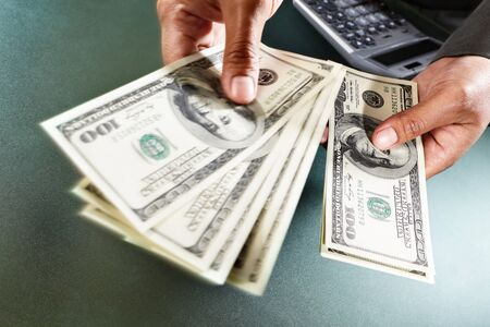 Busineswoman hand counting US dollar bills, taken close up photo