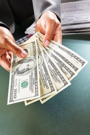 Busineswoman hand counting US dollar bills, taken close up
