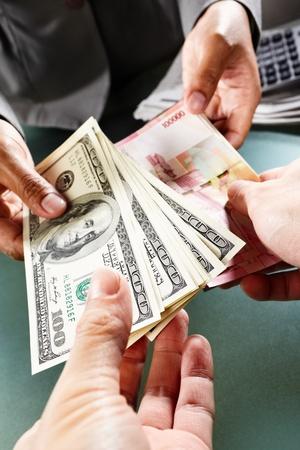 transaction: Twee mensen geld wisselen, een Amerikaanse dollar, een andere Rupiah
