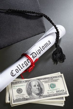 Graduation hat, and diploma certificate with a tack of US dollar bills for expensive education concept photo