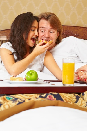 Couple enjoying breakfast together on bed in the morning Stock Photo - 9553537