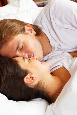 Happy couple showing their romance on fully covered white bed Stock Photo - 9553775
