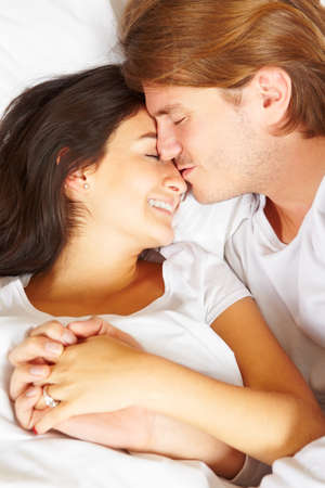 Happy couple showing their romance on fully covered white bed photo