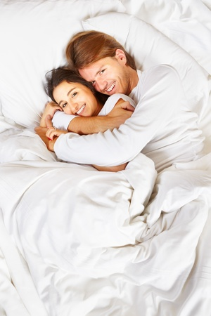 fully: Happy couple showing their romance on fully covered white bed