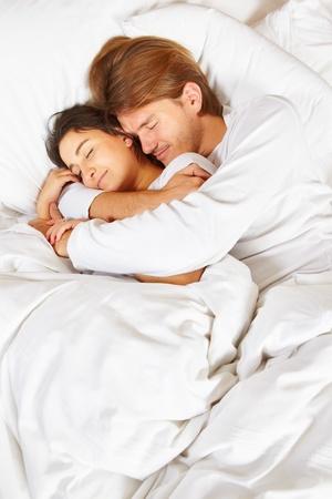pareja abrazada: Feliz pareja mostrando su romance en cama blanca totalmente cubierto