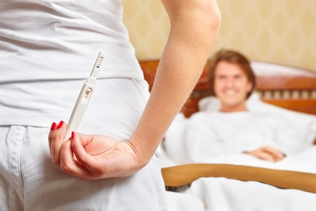 A lady is hiding her pregnancy test in front of her smiling spouse on bed Stock Photo