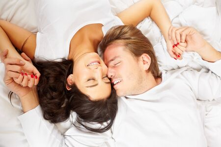 lying on bed: A happy romantic couple pose on whte covered bed, showing their love for each other