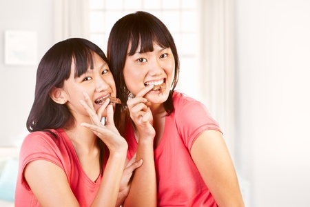 ni�as chinas: Dos ni�as chinas comiendo chocolate mirando la c�mara Foto de archivo