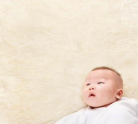 Chinese baby boy looking up to empty copy space of fur bed. Stock Photo - 9552896