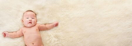 Chinese baby boy laying naked of fur bed with lot of copy space area on the right side. photo