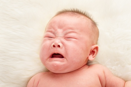 Chinese baby boy crying taken close up over fur bed Stock Photo - 9553333