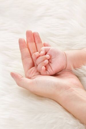 infant hand: Babys hand on mothers palm over soft fur background