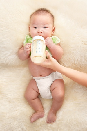 Chinese baby boy feeding milk from babys bottle Stock Photo