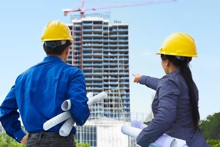 ingeniero civil: Dos contratistas, el hombre y la mujer que se enfrenta el proyecto de construcci�n en curso Foto de archivo