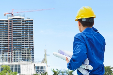 building plans: Male contractor or civil engineer looking at the bulding project on progress Stock Photo