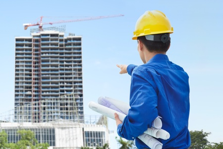 Male contractor or civil engineer looking at the bulding project on progress Stock Photo - 10000387