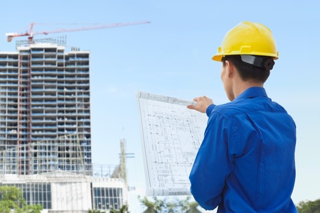 Male contractor or civil engineer looking at the bulding project on progress Standard-Bild