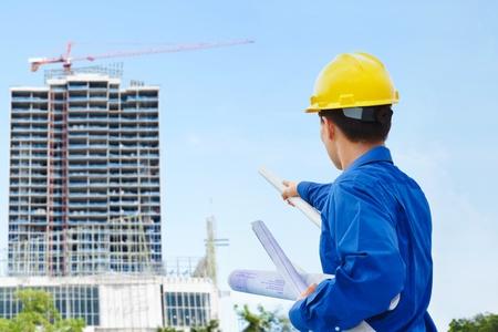 ingeniero civil: Contratista masculina o ingeniero civil mirando el proyecto de edificio en progreso